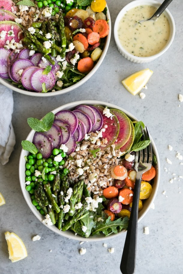Overhead shot of two bowls of salad with asparagus, peas, watermelon radishes, purple daikon, carrots, farro, and feta