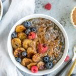 Overhead shot of a bowl of chia pudding with berries, caramelized bananas, and almond butter