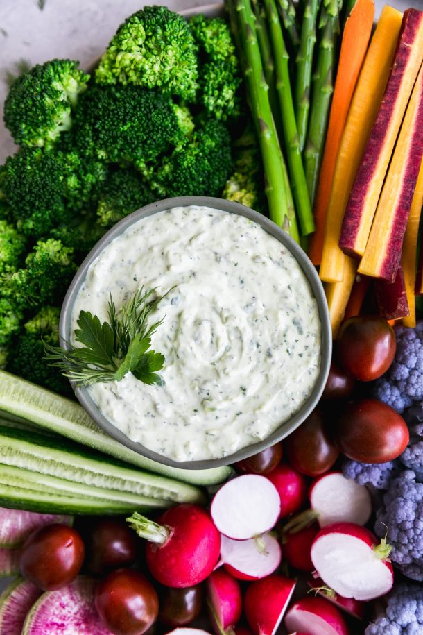 Close up shot of a colorful veggie platter with a bowl of creamy herb dip