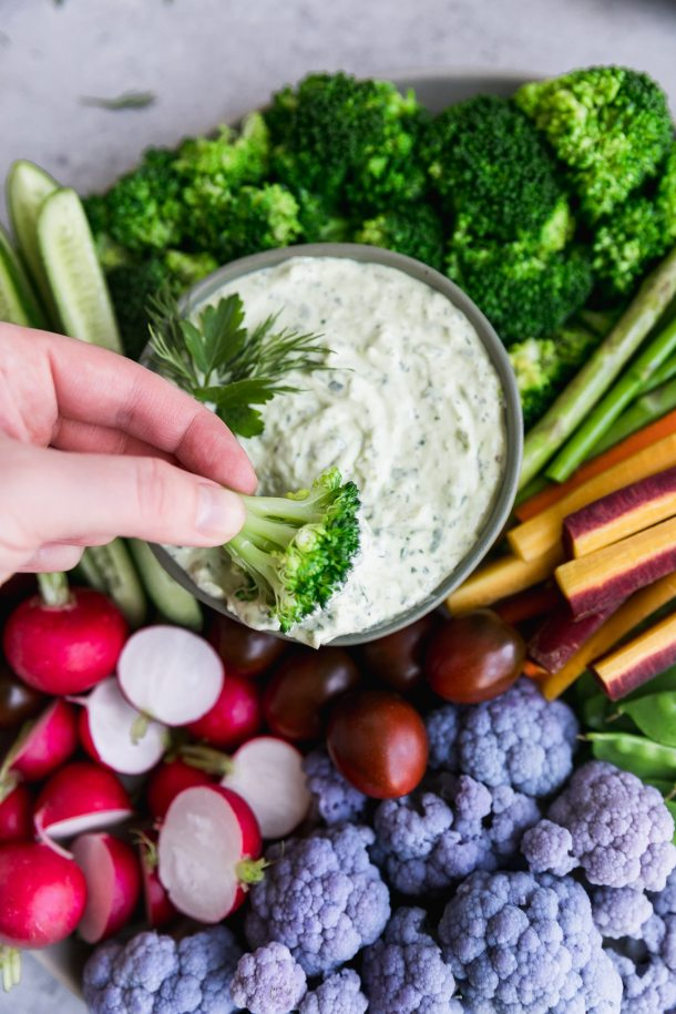 Close up shot of a colorful veggie platter and a hand dipping a piece of broccoli into a creamy dip
