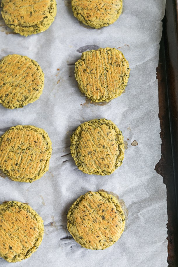 Overhead close up shot of a baking sheet with falafel arranged on it in rows