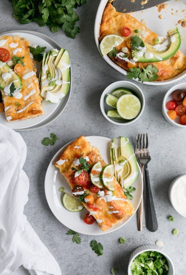 Overhead shot of two plates of enchiladas topped with halved cherry tomatoes, lime wedges, sour cream, and cilantro, with sliced avocado on the side