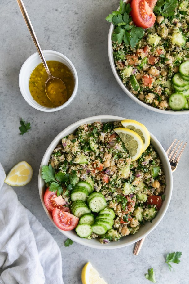 Overhead shot of two bowls of quinoa chickpea salad topped with sliced cucumbers, tomato, and lemon, with a small bowl of dressing off to the side