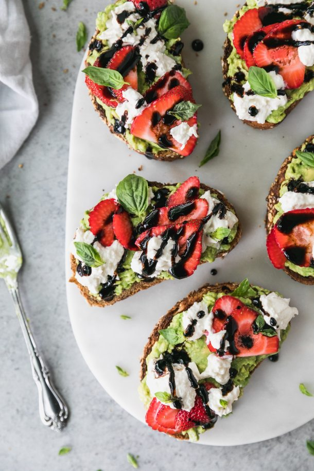 Overhead shot of five pieces of avocado toast topped with burrata cheese, sliced strawberries, fresh basil, and balsamic glaze, with a fork off to the lefthand side