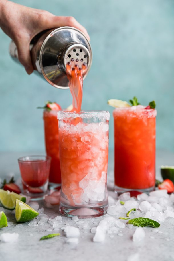 Forward facing shot of a strawberry margarita being poured into a tall glass filled with crushed ice, with two strawberry margaritas in the background
