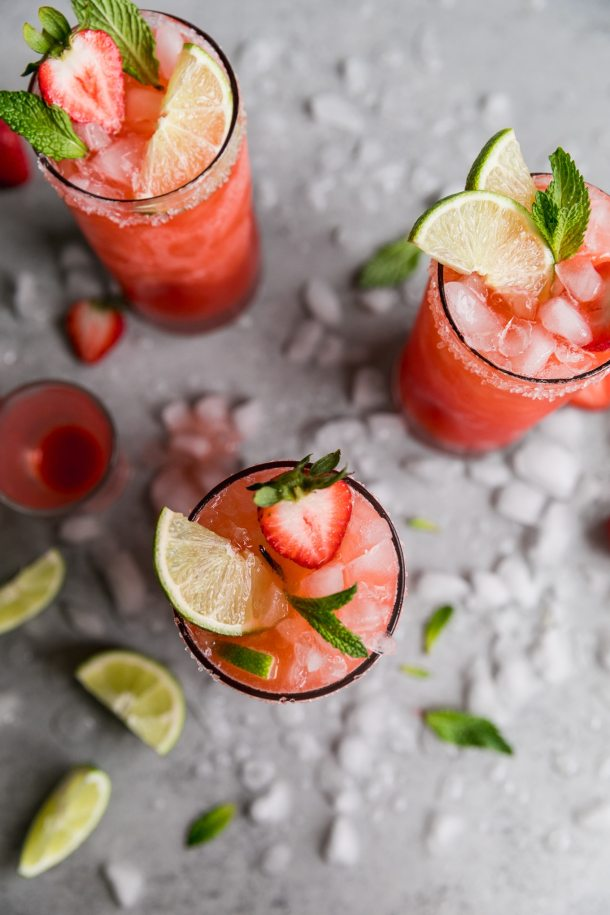 Overhead shot of three strawberry margaritas garnished with halved strawberries, mint and lime wedges, with crushed ice on the table