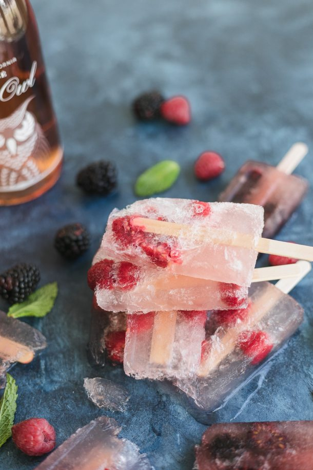 Close up shot of raspberry frosé popsicles stacked on top of each other on a blue background and berries and mint scattered around and a rosé wine bottle off to the left side