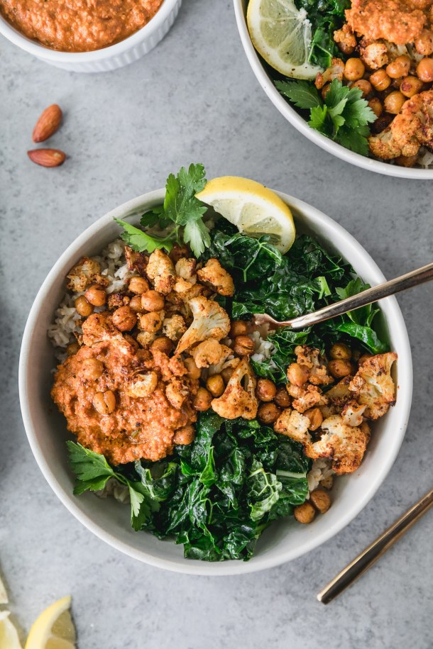 Overhead shot of a bowl of sautéed kale with roasted chickpeas and cauliflower, with a scoop of romesco sauce and a fork sticking out of the bowl