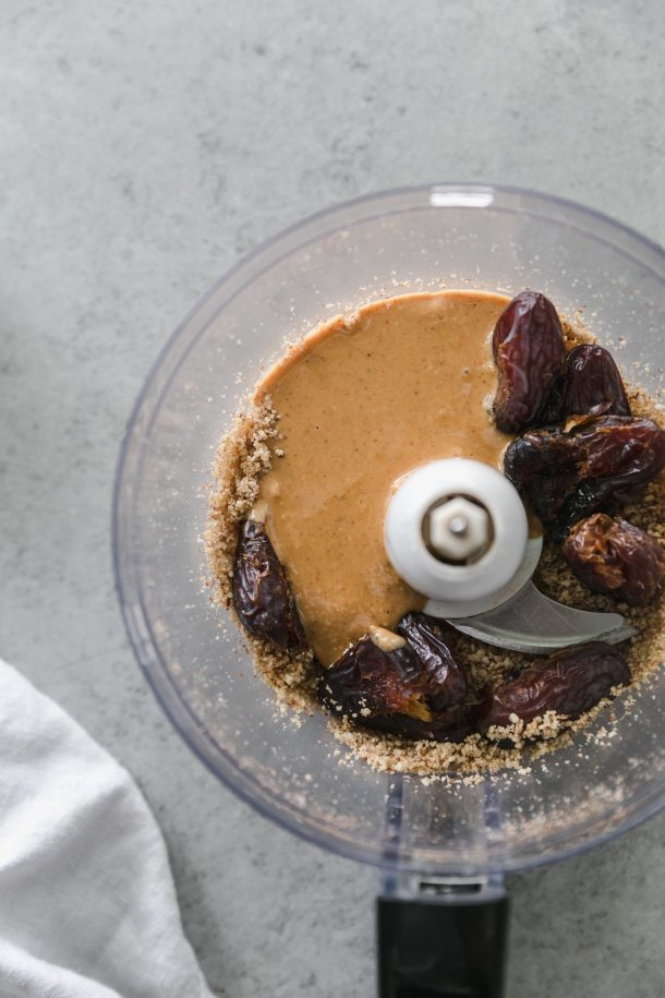 Overhead shot of a food processor filled with dates, pulsed nuts, and peanut butter