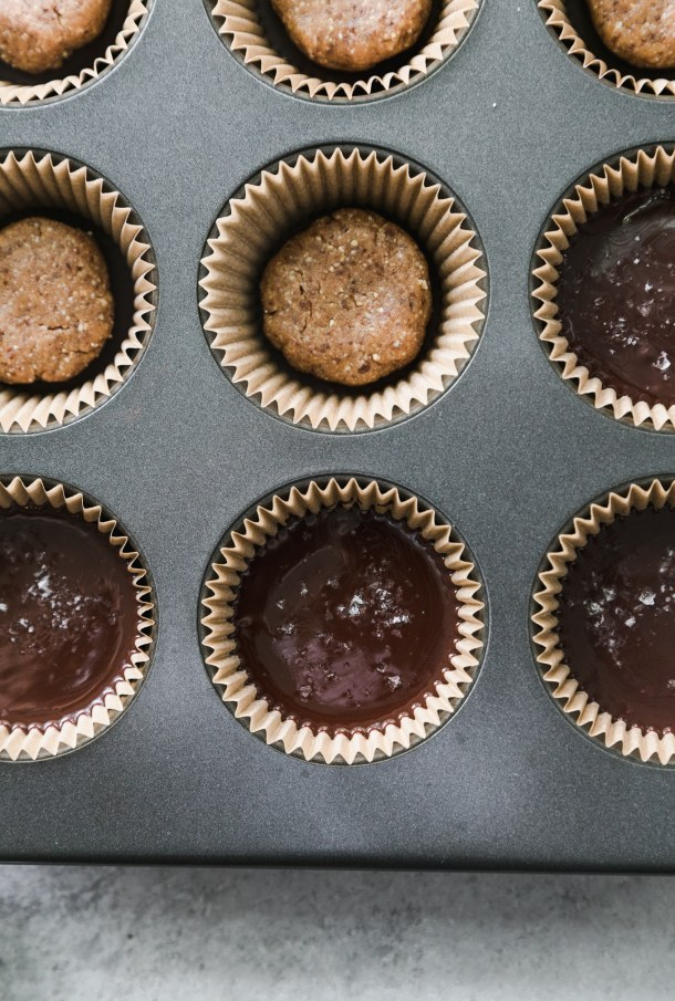 Overhead shot of a muffin tin filled with dark chocolate peanut butter cups being made