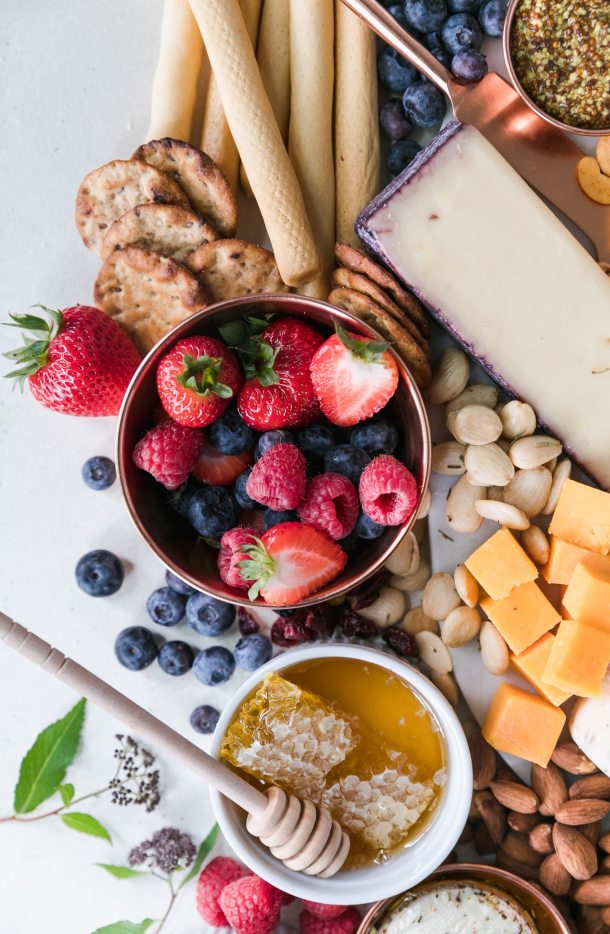 Overhead close up shot of a bowl of fresh berries alongside assorted cheeses and crackers, with a bowl of honey and honeycomb below it