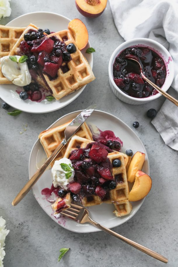 Overhead shot of two plates of waffles with peach blueberry compote on top, with a bite taken out of the waffles on the lower plate and a bowl of compote in the top right