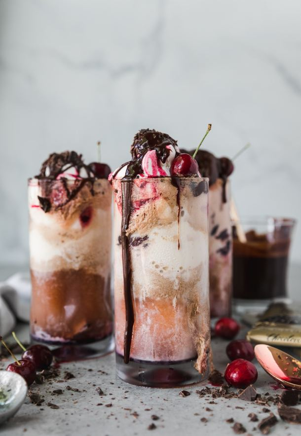 Forward facing shot of a chocolate cherry bourbon float garnished with chocolate fudge sauce, whipped cream, and cherries with two more floats behind it and a glass of chocolate fudge sauce