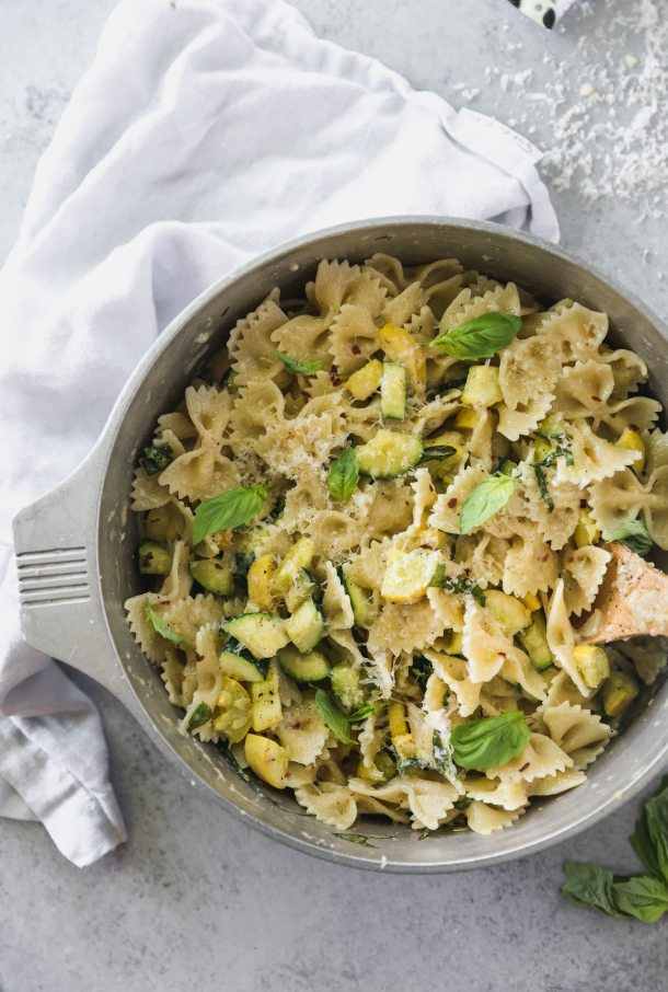 Overhead shot of a pot filled with bow tie pasta with zucchini, summer squash, and basil with a wooden spoon in the pot