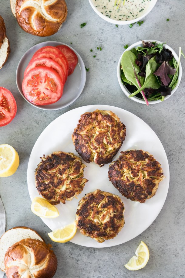 Overhead shot of a white plate with 4 crab cakes on it, a small grey plate with sliced tomatoes on it, and a small bowl of lettuce, with a lemon half and lemon wedges