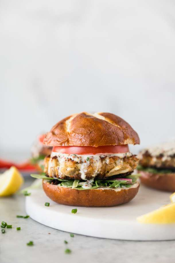Forward facing shot of a crab cake sandwich with lettuce, tomato, and chive honey mustard sitting on a marble board with lemon wedges next to it