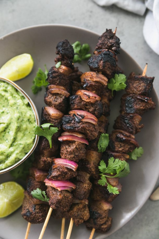 Overhead close up shot of a plate with steak and red onion skewers on it sprinkled with cilantro and a bowl of green avocado salsa on the left