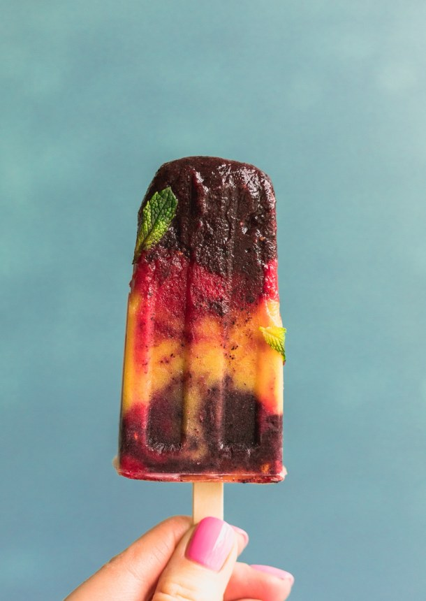 Close up forward facing shot of a layered blueberry, raspberry and mango popsicle with a mint leaf on it against a blue background