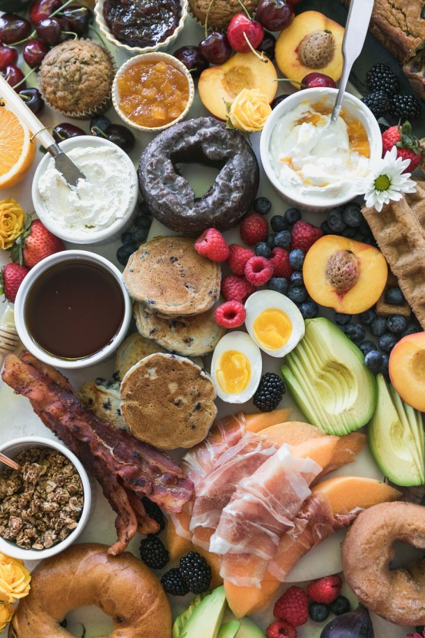 Overhead close up shot of a colorful brunch board filled with doughnuts, muffins, chocolate chip banana bread, fruit, mini pancakes, waffle sticks, yogurt, prosciutto wrapped melon, avocado, soft boiled eggs, bacon, granola, and bagels