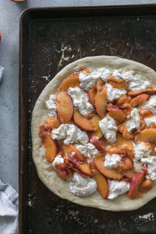Overhead shot of rolled out pizza dough on a baking sheet topped with sliced peaches, chunks of burrata, and orange zest