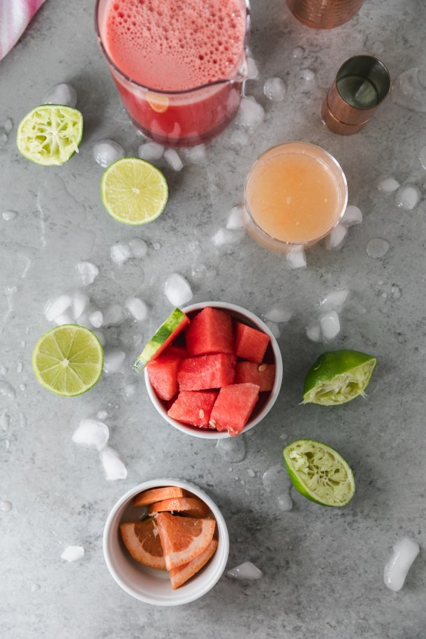 Overhead shot of a bowl of cubed watermelon, squeezed limes, a cup of grapefruit juice, and a bowl of sliced grapefruit with crushed ice scattered around