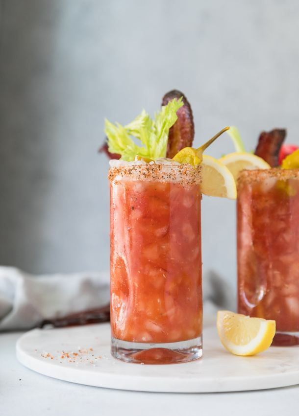 Forward facing shot of 2 bloody marys garnished with lemon, celery, and candied bacon