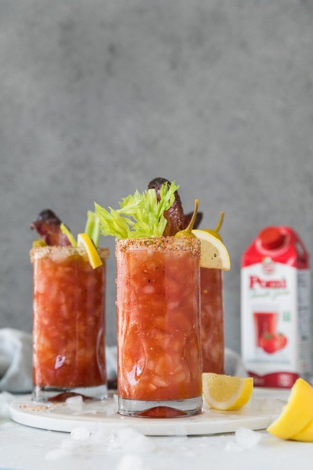 Forward facing shot of 3 bloody marys garnished with lemon, celery, and candied bacon with a carton of tomato juice in the background