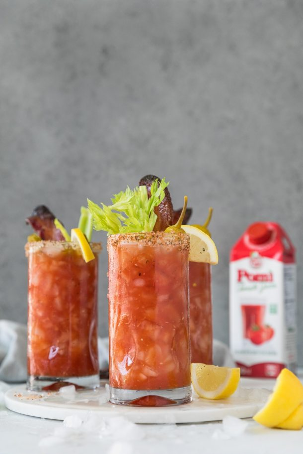 Forward facing shot of 3 bloody marks garnished with lemon, celery, and candied bacon with a carton of tomato juice in the background