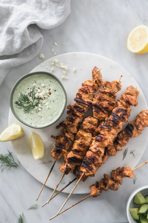 Overhead shot of a pile of grilled chicken skewers with a bowl of light green tzatziki and lemon wedges next to it