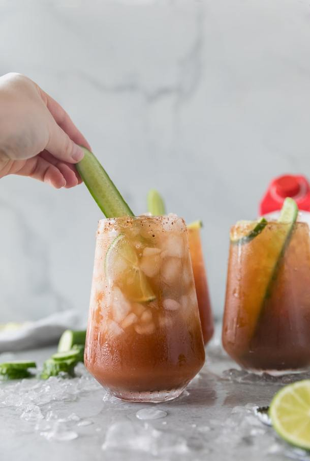 Forward facing close up shot of 3 michelada cocktails with a hand putting a cucumber spear in one of them