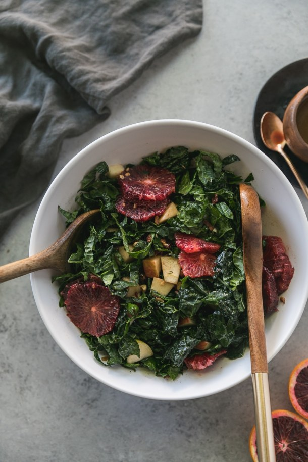 Overhead shot of a white mixing bowl filled with kale salad with blood oranges and apples, with wooden salad spoons with gold handles in the bowl