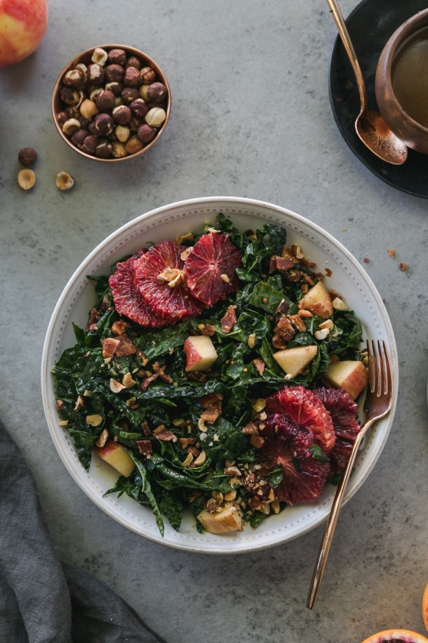 Overhead shot of a bowl of kale salad with blood oranges, apples, chopped bacon, and hazelnuts with a gold fork resting in the bowl and a ramekin of hazelnuts above it