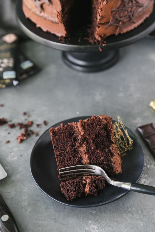 Close up shot of a piece of chocolate cake on a black plate with a fork taking a bite out of it