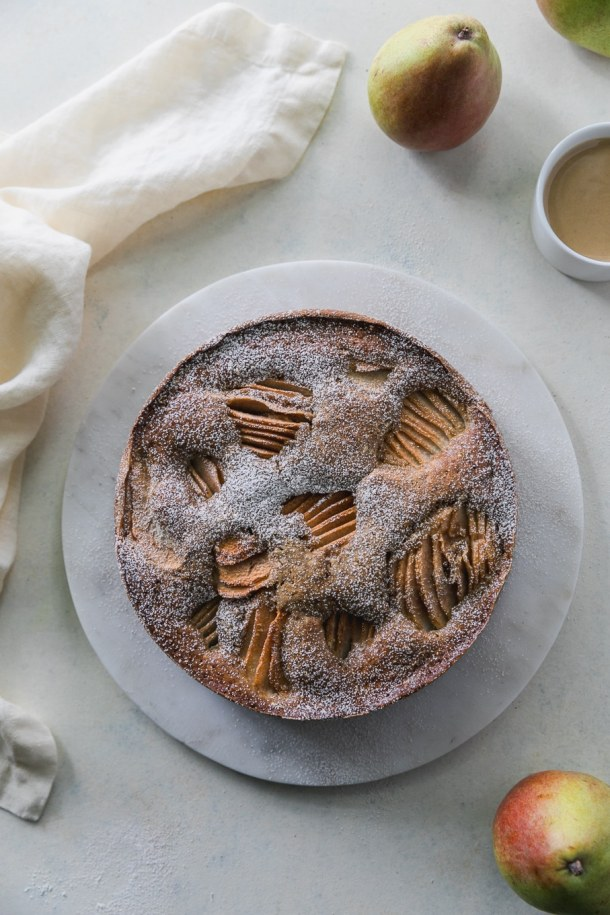 Overhead shot of a pear cake dusted with powdered sugar with pears in the bottom and top right the frame, as well as a ramekin of tahini