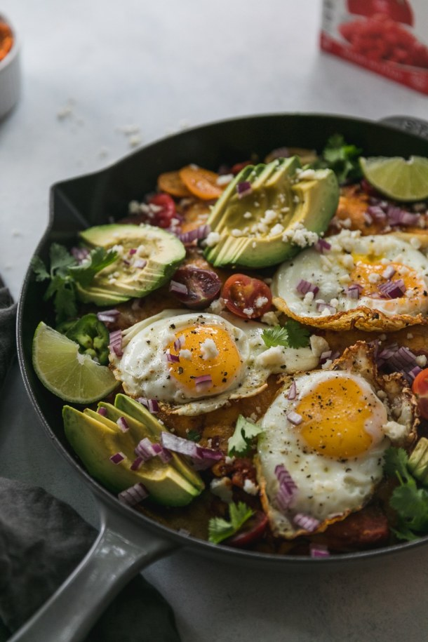 Close up shot of a black skillet filled with chilaquiles, fried eggs, avocado, cilantro, and tomatoes