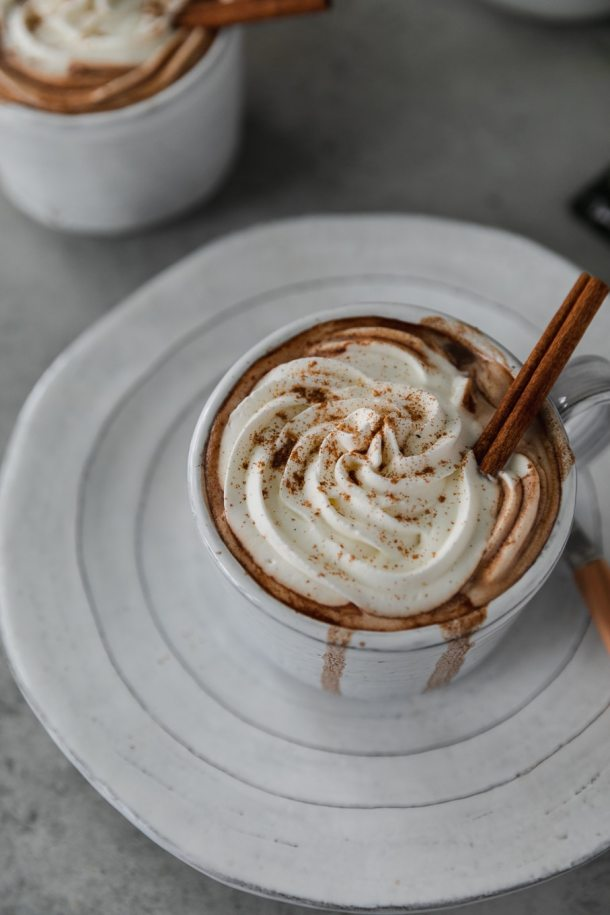 Close up shot of a white mug filled with hot chocolate on a white plate, topped with whipped cream, a pinch of pumpkin pie spice, and a cinnamon stick