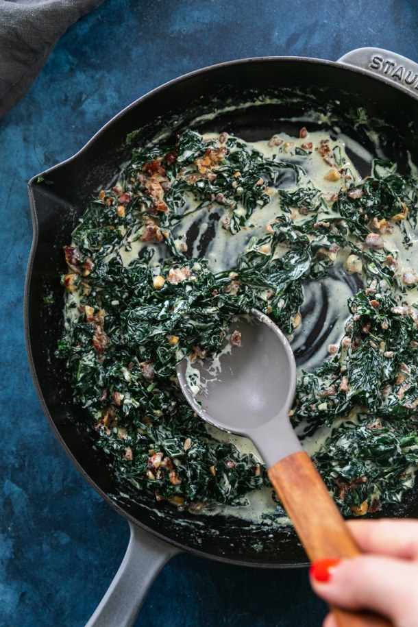 Overhead shot of a cast iron skillet filled with creamed kale and hazelnut bacon crunch and a spoon stirring it