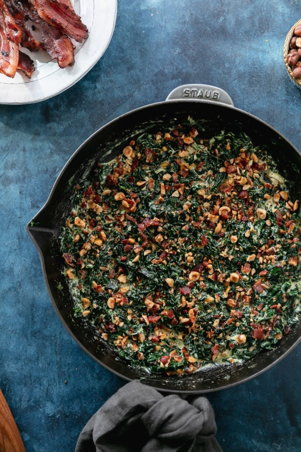 Overhead shot of a cast iron skillet filled with creamed kale and hazelnut bacon crunch with a plate of bacon in the upper left