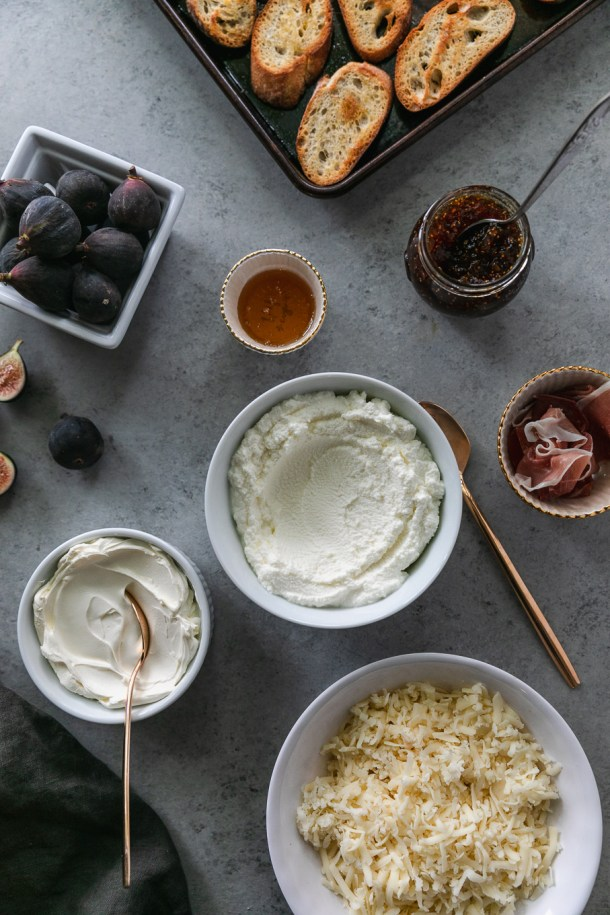Overhead shot of a bowl of ricotta, a bowl of mascarpone, a bowl of shredded cheese, and ramekins filled with prosciutto, honey, and fig preserves, and a basket of figs in the top left