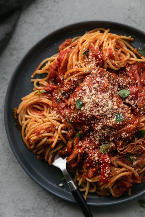 Overhead close up shot of a plate of chicken cacciatore over pasta with a fork twirling noodles resting on the plate