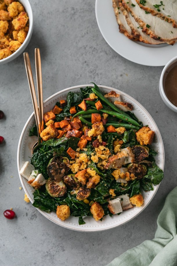 Overhead shot of a thanksgiving leftovers kale salad with roasted sweet potatoes, brussels, green beans, and cornbread croutons