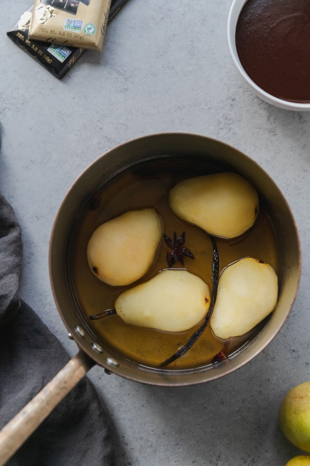 Overhead shot of a saucepan with 4 poached pears in it with a vanilla bean and a star anise pod floating in it
