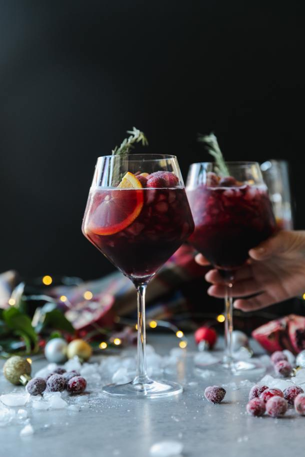 Forward facing shot of a wine glass filled with red sangria, garnished with a rosemary sprig, with another glass behind it with a hand reaching out to pick it up, with crushed ice, christmas ornaments, a plaid scarf, and twinkle lights in the background