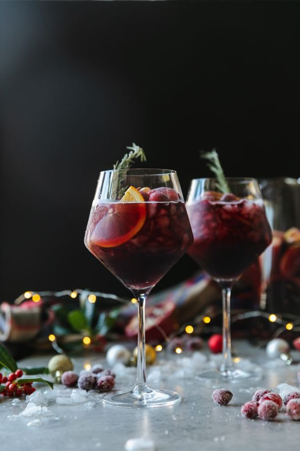 Forward facing shot of a wine glass filled with red sangria, garnished with a rosemary sprig, with another glass behind it, with crushed ice, christmas ornaments, a plaid scarf, and twinkle lights in the background