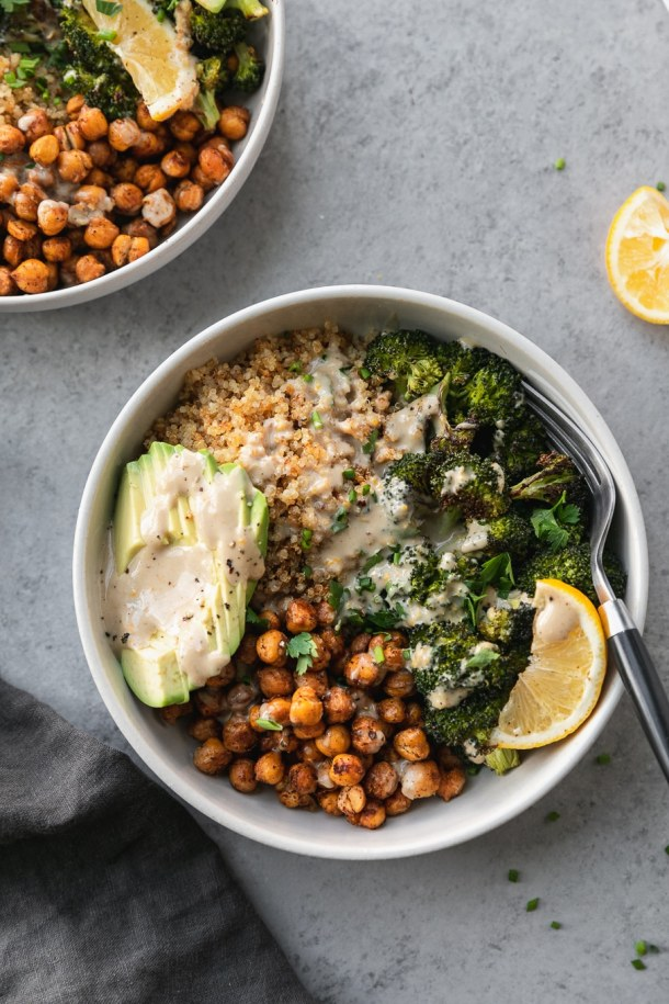 Overhead shot of a bowl with quinoa, chickpeas, roasted broccoli, sliced avocado, a lemon wedge, and tahini sauce with a black and silver fork in the bowl