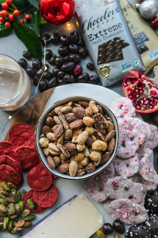 Overhead close up shot of a bowl of mixed nuts surrounded by white chocolate peppermint covered pretzels, pomegranate, chocolate, pistachios, cookies, and a glass of irish cream on the rocks