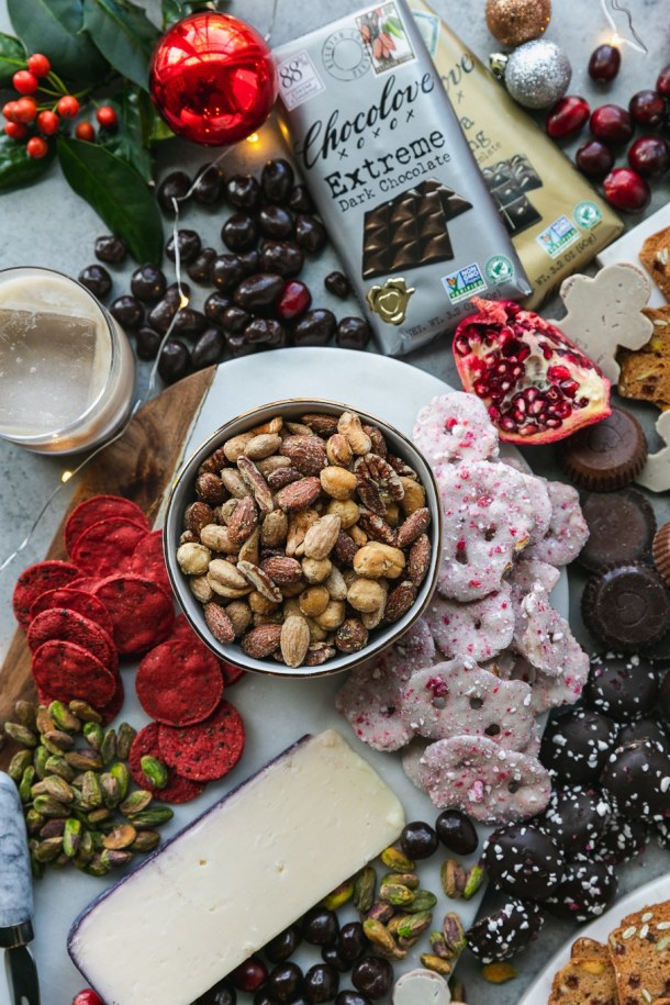 Overhead shot of a bowl of mixed nuts surrounded by white chocolate peppermint covered pretzels, pomegranate, chocolate, pistachios, cookies, and a glass of irish cream on the rocks