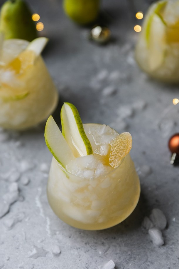 Close up shot of a glass of pear ginger champagne punch garnished with pear slices and crystallized ginger against a grey background with crushed ice scattered around