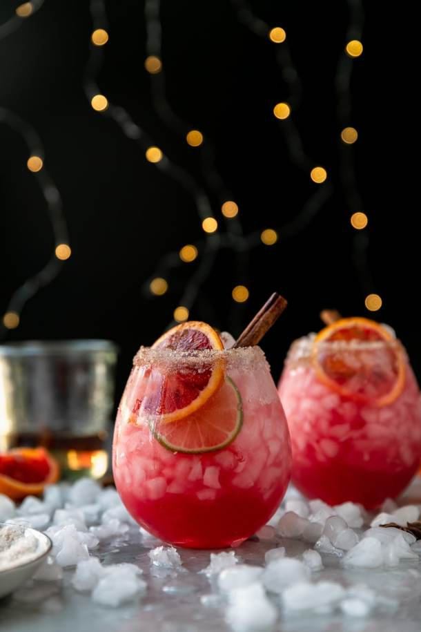 Forward facing shot of 2 pink blood orange cocktails against a black background with twinkle lights