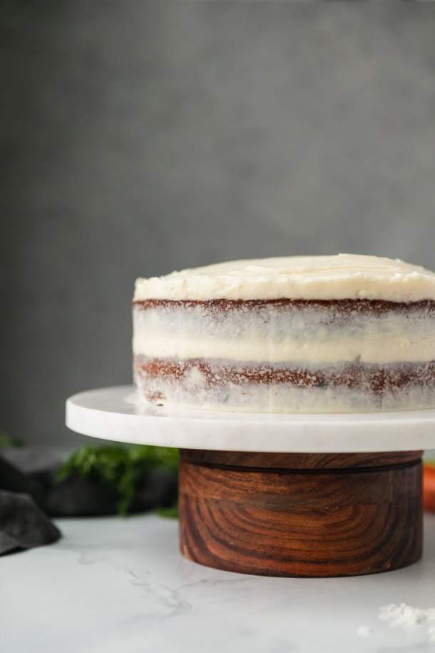 Forward facing shot of a carrot cake on a marble and wooden cake stand